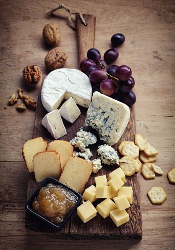 Cheese plate served with grapes, jam, crackers and nuts on a wooden background