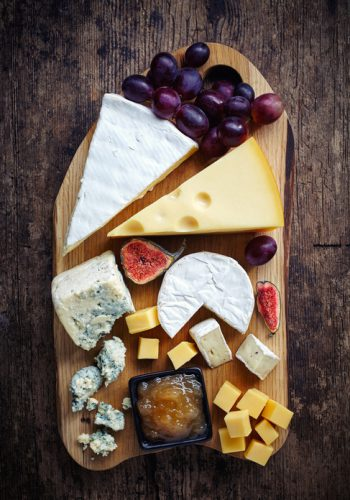 Cheese plate served with grapes, jam and figs on a wooden background